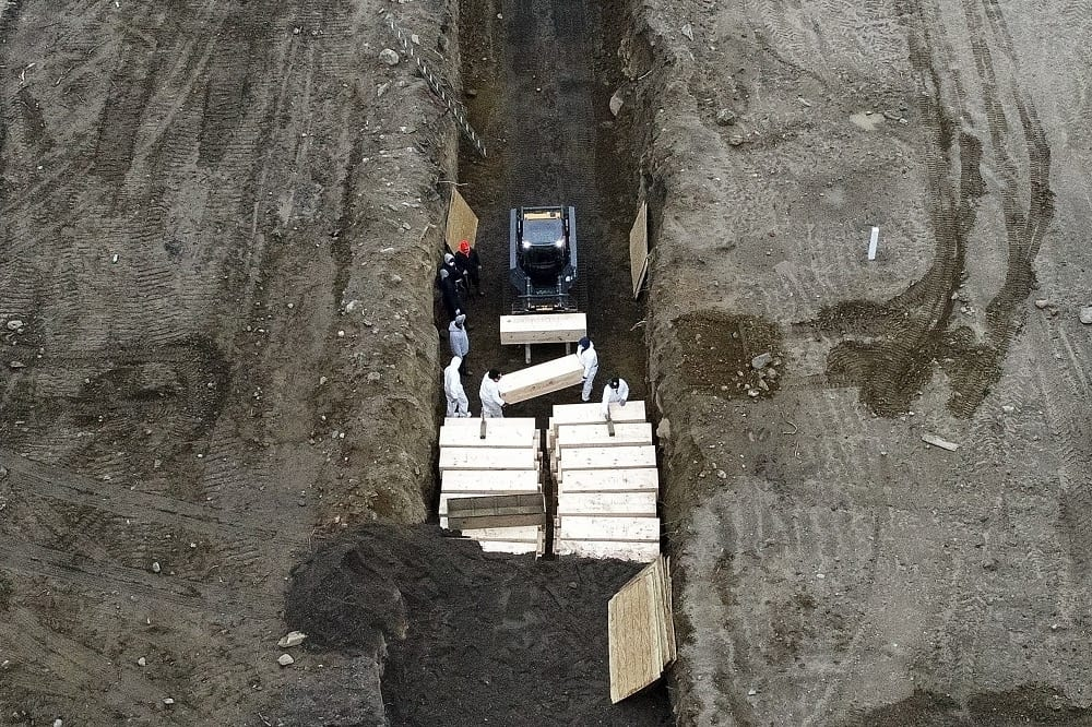 Workers wearing personal protective equipment bury bodies in a trench on Hart Island, Thursday, April 9, 2020, in the Bronx borough of New York. On Thursday, New York City's medical examiner confirmed that the city has shortened the amount of time it will hold on to remains to 14 days from 30 days before they will be transferred for temporary internment at a City Cemetery. Earlier in the week, Mayor Bill DeBlasio said that officials have explored the possibility of temporary burials on Hart Island, a strip of land in Long Island Sound that has long served as the city's potter's field. (AP Photo/John Minchillo)