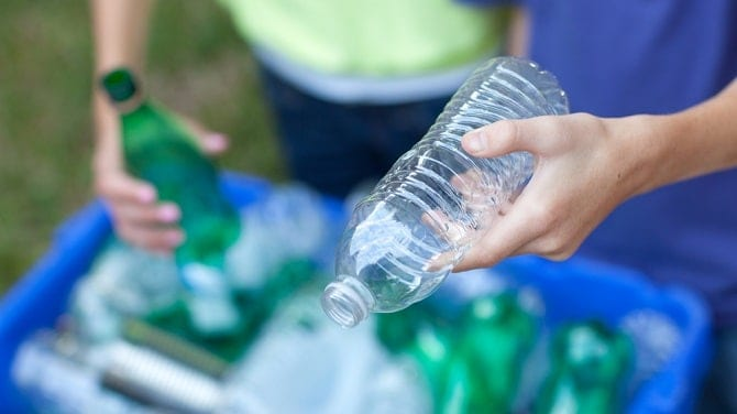 Caucasian boy and girl putting clear and green bottles and metal cans in recycling blue bin outside in yard