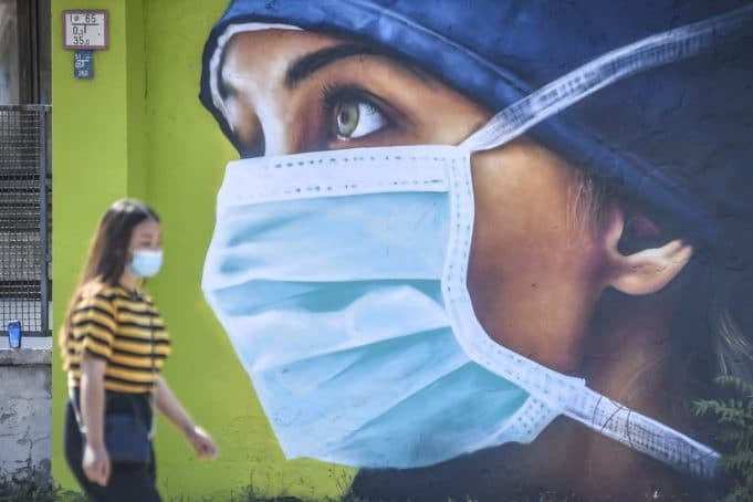 A woman wearing a protective mask walks by one of the murals dedicated to medical personnel of the Sacco infectious diseases hospital that fought the COVID-19, created by the artist Cosimo Cheone in Milan, Italy, Tuesday, July 21, 2020. (Claudio Furlan/LaPresse via AP)