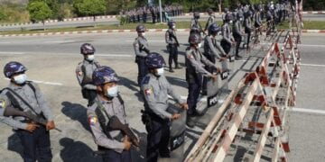 Policemen wearing protective face mask stand guard behind a road barricade, as a part of security preparations ahead of next week's opening of Myanmar's parliament in Naypyitaw, Myanmar, Friday, Jan. 29, 2021. Myanmar's election commission rejected allegations by the military that fraud played a significant role in determining the outcome of November's elections, which delivered a landslide victory to Aung San Suu Kyi's ruling party.(AP Photo/Aung Shine Oo)